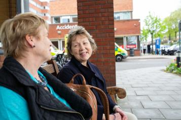 Two women talking to each other outside a hospital